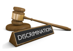 photo of a gavel and a sign of discrimination